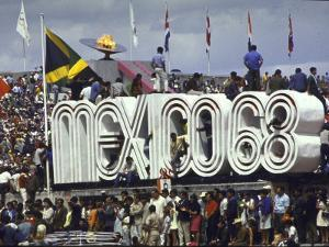 People Climbing and Sitting on a Mexico '68 Sign at the Summer Olympics by John Dominis