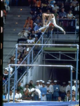 Soviet Gymnast Olga Korbut in Action on the Uneven Bars at the Summer Olympics by John Dominis