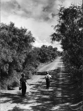 Two Children Walking Down a Dirt Road Going Fishing on a Summer Day by John Dominis