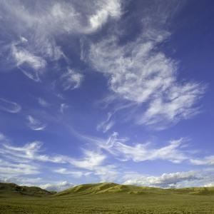 Lofty cumulus and cirrus clouds over sagebrush prairie by John Eastcott & Yva Momatiuk