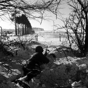 American Soldier Peering Across Snowy Field During Counter Offensive Known as Battle of the Bulge by John Florea