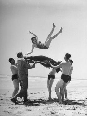 Army Men Bouncing Starlet Majorie Woodworth Into the Air by John Florea