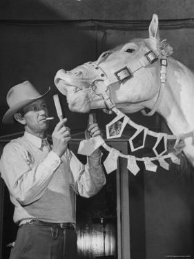 """Groom Cleaning Horse's Teeth During Filming of the Movie """"The Ziegfeld Follies"""" by John Florea"""