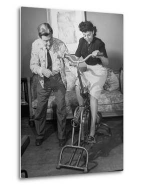 Producer-Director Preston Sturges and His Secretary Trying Out an Exercise Bicycle by John Florea