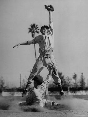 Red Sox's Player in Mid Air Catching the Ball, While an Opposing Player Slides Between His Legs by John Florea