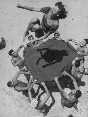 Teenaged Boys Using Blanket to Toss Their Friend, Norma Baker, Into the Air on the Beach by John Florea