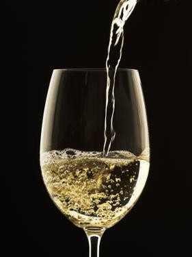 White Wine Pouring from Bottle into Glass by John Hay