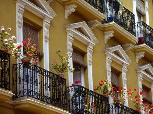 Spain, Sevilla, Andalucia Geraniums hang over iron balconies of traditional houses by John & Lisa Merrill
