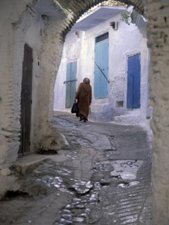 Traditionally Dressed Woman along Cobblestone Alley, Morocco