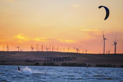 Usa, California, Rio Vista. Kiteboarder at sunset with wind farm turbines. by John & Lisa Merrill