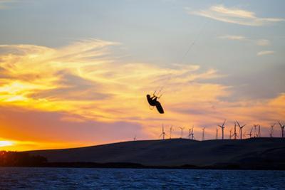 USA, California, Rio Vista, Sacramento River Delta. Kiteboarder catching air at sunset. by John & Lisa Merrill