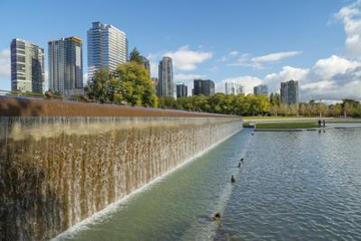 USA, Washington State, Bellevue. Pond and waterfall at Downtown Park, with skyline. by John & Lisa Merrill