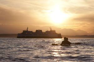USA, Washington State, Seattle. Two-person sea kayak in Elliott Bay at sunset. by John & Lisa Merrill
