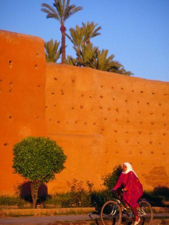 Veiled Woman Bicycling Below Red City Walls, Marrakech, Morocco by John & Lisa Merrill