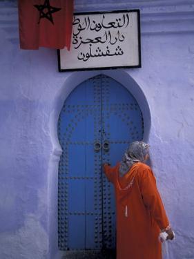 Woman Exits thru Moorish-Style Blue Door, Morocco by John & Lisa Merrill