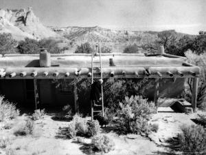 Georgia O'Keeffe Climbing a Ladder Outside Ghost Ranch, Her Desert Home by John Loengard