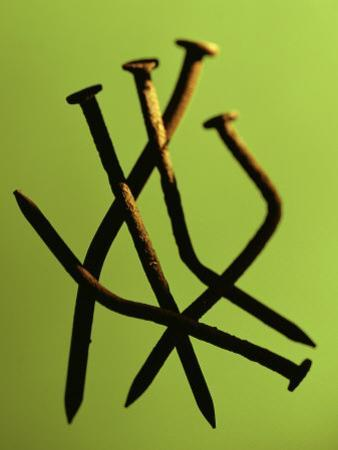 Five Rusty Nails Against a Green Background