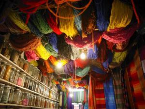 Brightly Dyed Wool Hanging from Roof of a Shop, Marrakech, Morrocco, North Africa, Africa by John Miller