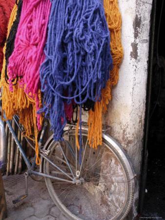 Brightly Dyed Wool Hanging Over Bicycle, Marrakech, Morrocco, North Africa, Africa by John Miller