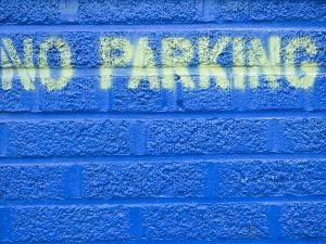 Painted Blue Brick Wall with No Parking Sign by John Nordell