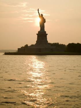 Sun Setting Behind the Statue of Liberty on a Summer Evening by John Nordell