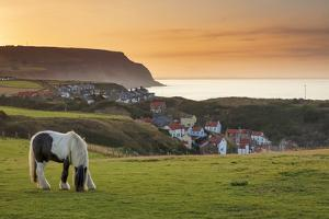 Staithes fishing village and distant Boulby Cliffs, England by John Potter