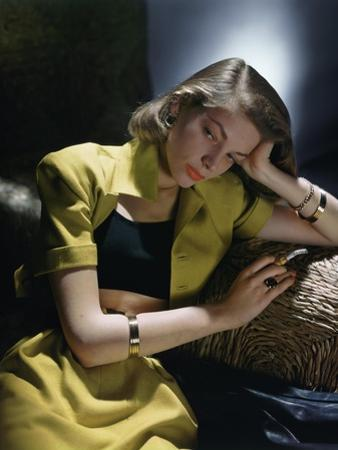 Actress Lauren Bacall Wearing Yellow Bare-Midriff Suit with Black Halter from B. H. Wragge by John Rawlings