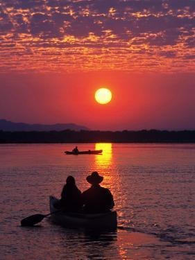 Canoeing at Sun Rise on the Zambezi River by John Warburton-lee