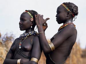 Dassanech Girl Braids Her Sister's Hair at Her Village in the Omo Delta by John Warburton-lee