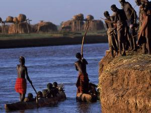 Dassanech Tribesmen and Women Load into a Dugout Canoe Ready to Pole across the Omo River, Ethiopia by John Warburton-lee