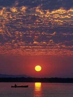 Lower Zambesi National Park, Canoeing on the Zambezi River at Sun Rise under a Mackerel Sky, Zambia by John Warburton-lee