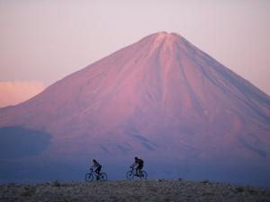 Mountain Biking in Atacama Desert Against a Backdrop of Perfect Cone of Volcan Licancabur 5916 M by John Warburton-lee