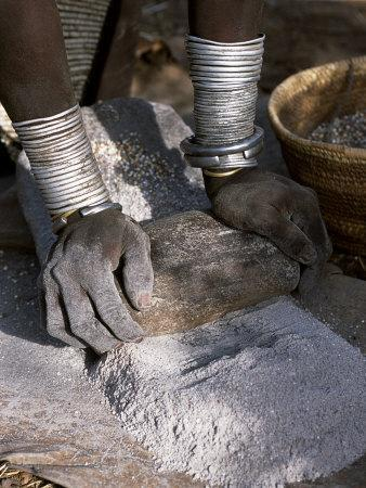 Nyagatom Woman Grinds Sorghum Using Two Stones, Omo River, South-Western Ethiopia