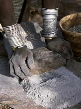 Nyagatom Woman Grinds Sorghum Using Two Stones, Omo River, South-Western Ethiopia by John Warburton-lee