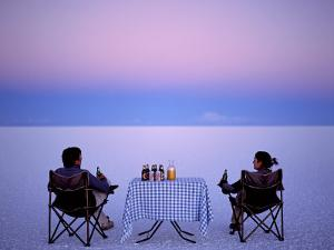 Tourists Enjoy Sundowners While Looking Out across the Endless Salt Crust of Salar De Uyuni by John Warburton-lee