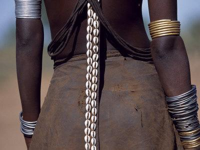 Young Dassanech Girl Wears a Leather Skirt, Metal Bracelets, Amulets and Bead Necklaces, Ethiopia