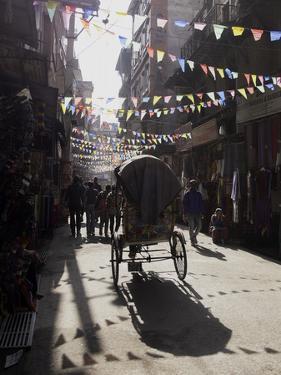 A Rickshaw Driving Through the Streets of Kathmandu, Nepal, Asia by John Woodworth