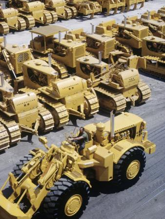 Rows of Brightly Colored Caterpillar Bulldozers Lined up at an Unidentified Factory
