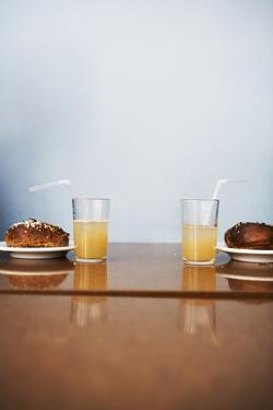 Two Cinnamon Buns and Two Glasses of Lemonade in a Cafe, Sweden. by Johner Images