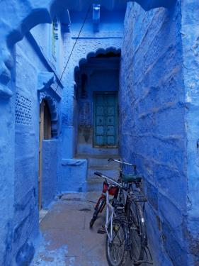 Bicycles Parked in Blue-Painted Laneway by Johnny Haglund