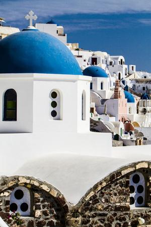 Oia, Greece. Row of Greek Orthodox Churches with blue domes.