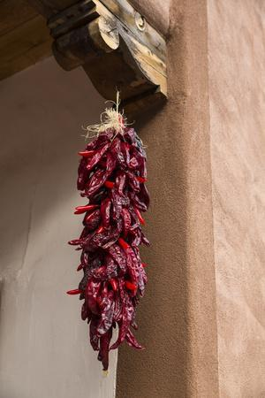 Santa Fe, New Mexico. Long, red chili, hanging from a wooden corbel and stucco wall