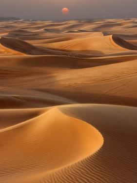 Sunset over the sand dunes in Dubai by Jon Bower