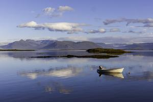A Johnboat with An Outboard Motor and Its Reflection in Calm Blue Water by Jonathan Irish