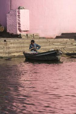 A Man in a Rowboat in Water Tinted Pink by Reflections of a Pink Wall by Jonathan Irish