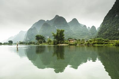 A Barefoot Man Walks Across the Li River Near Yangshuo, China by Jonathan Kingston
