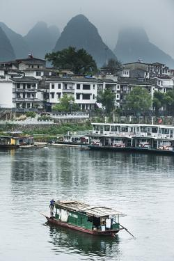 A Boat Crosses the Lijiang River on a Foggy Day in Yangshuo, China by Jonathan Kingston