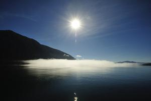A Layer of Fog Hangs over the Waters of the Inside Passage on a Sunny Day by Jonathan Kingston