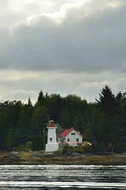A Lighthouse on a Rocky Point under a Cloud-Filled Sky by Jonathan Kingston