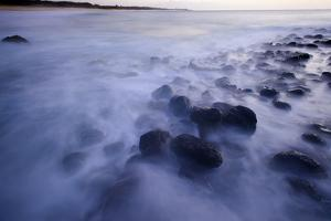 A Long Exposure Makes Waves Look Like Mist Breaking over Rounded Volcanic Rocks by Jonathan Kingston